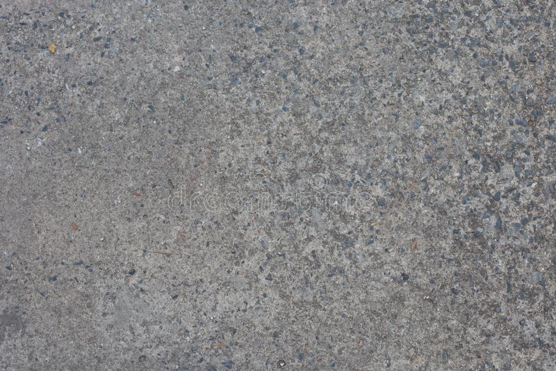 Pavimento di calcestruzzo con le rocce nel calcestruzzo immagine stock libera da diritti