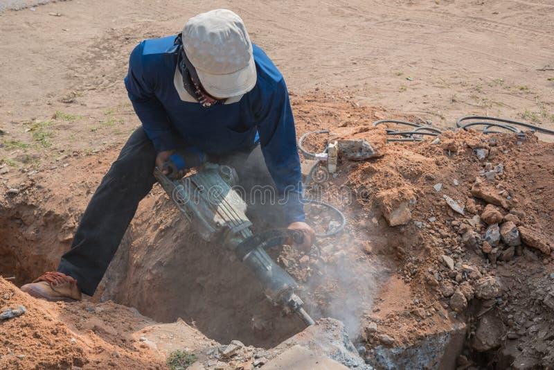 Pavimento di calcestruzzo del cemento di perforazione del lavoratore con la macchina immagini stock