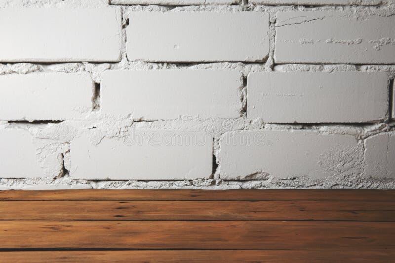 pavimento di legno della plancia marrone con il muro di mattoni bianco immagine stock