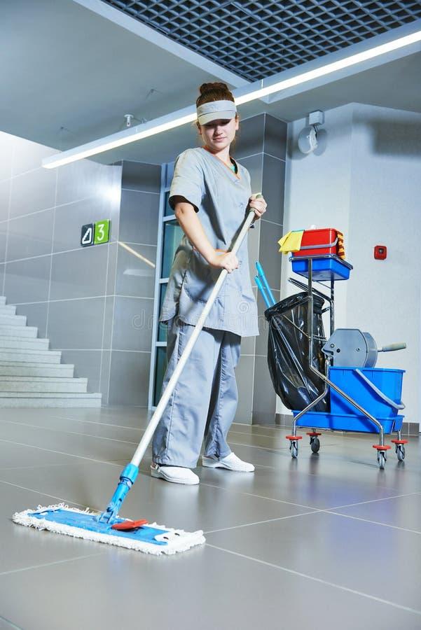 Pavimento di pulizia del lavoratore con la macchina immagine stock