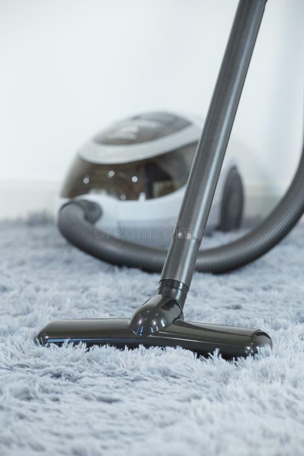 Pavimento di tappeto di pulizia con l'aspirapolvere nel salone immagine stock libera da diritti