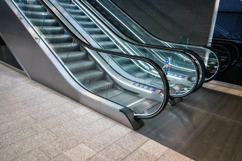 Pavimento mais inferior perto das escadas rolantes vazias iluminadas na construção moderna imagem de stock