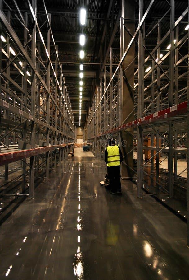 Pavimento di sfregatura del lavoratore in magazzino vuoto fotografia stock libera da diritti