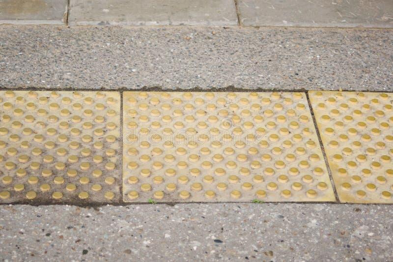 Pavimento táctil amarillo de las tejas para la gente ciega imágenes de archivo libres de regalías