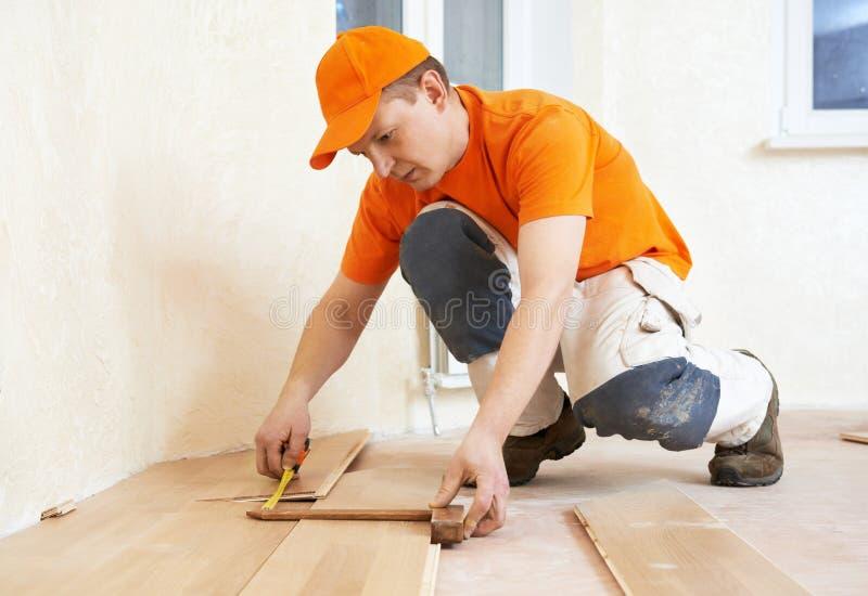 Pavimento unentesi del parket del lavoratore del carpentiere immagine stock libera da diritti