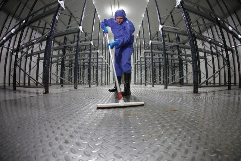 Pavimento uniforme di pulizia dell'operaio in deposito immagini stock libere da diritti