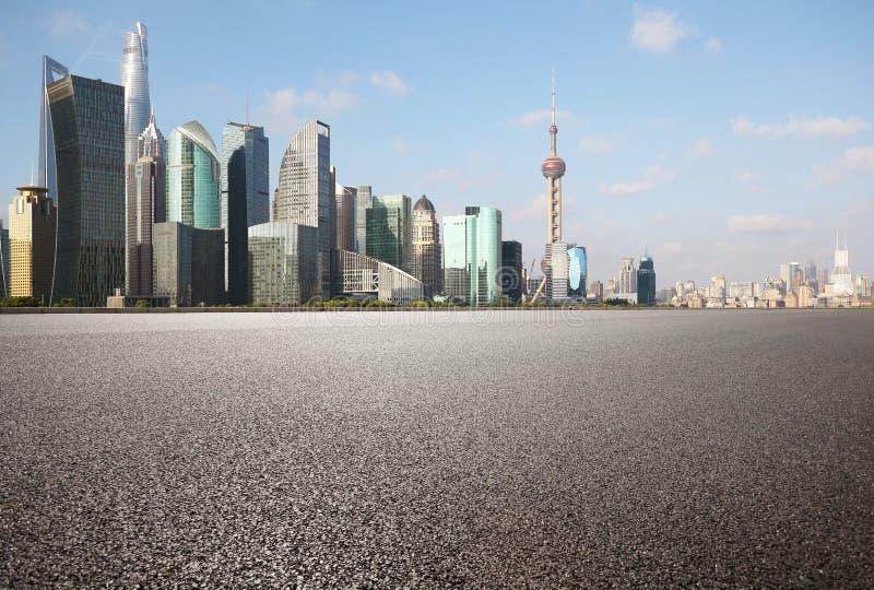 Pavimento vuoto del fondo stradale con le costruzioni del punto di riferimento della città di Shangha immagine stock libera da diritti