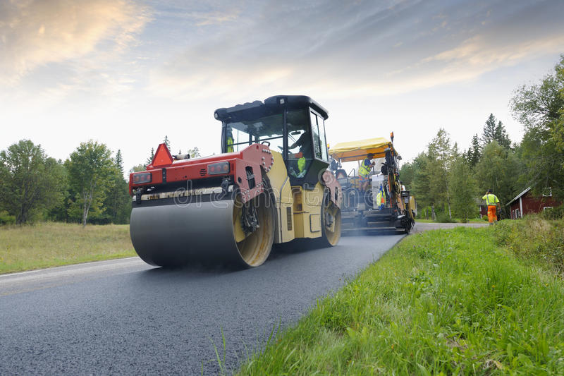 Paving machine crew at road-works stock images