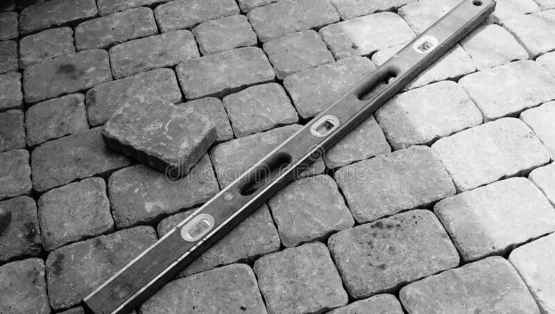 Paving stones have been laid down for a patio. A photograph of paving stones and a level after paving a nice outdoor patio in black and white stock image