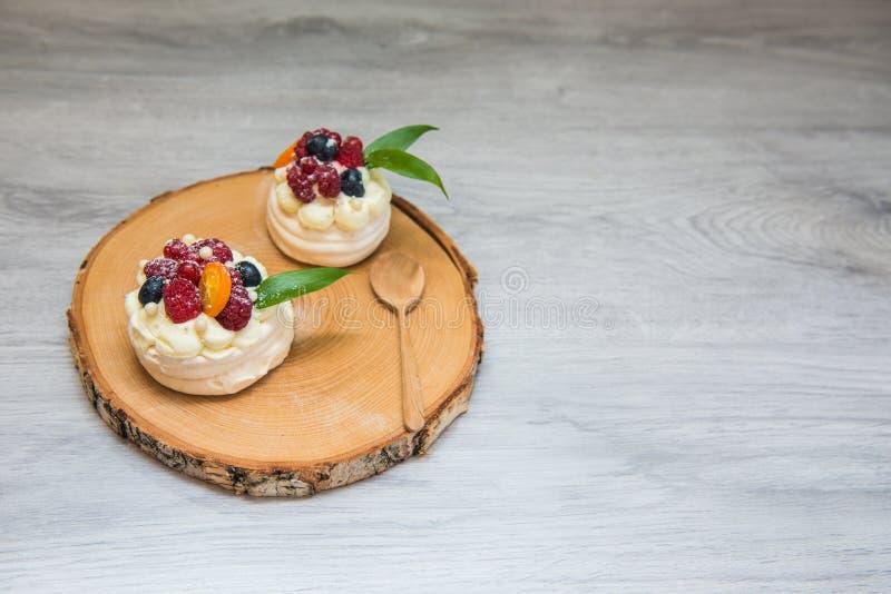 Pavlova bezy tort z kremowymi i małymi owoc obrazy stock