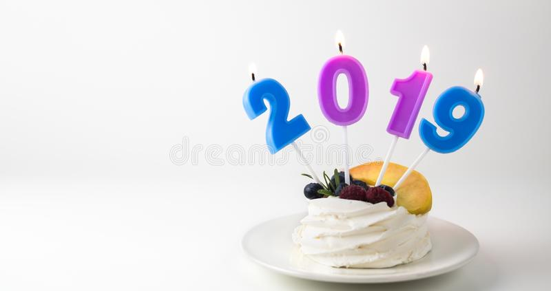 Pavlova cake with blueberries, raspberries and peaches and burning candles 2019 on bright white background in plate. stock photography