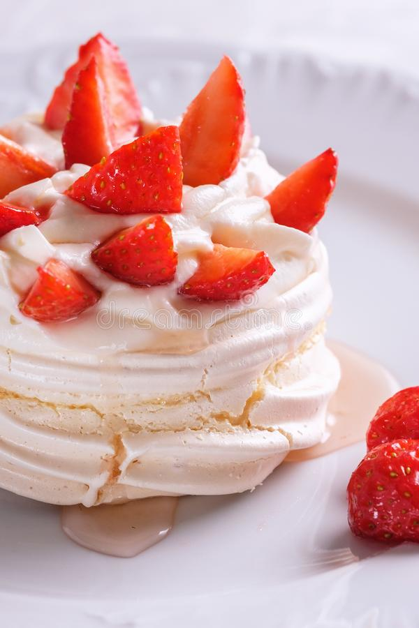 Pavlova dessert with strawberries on a white plate royalty free stock images