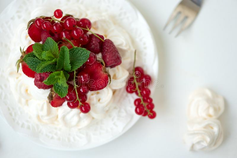 Pavlova fruit cake with strawberry, raspberry, red currant and mint leaves on white background. Selective focus. Healthy food stock photos