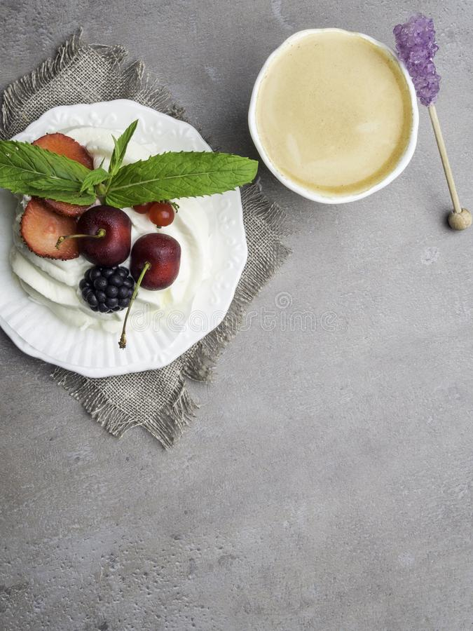 Delicious Pavlova cake with alternating layers of whipped cream and meringue topped with fresh berries, and coffee cup with fresh royalty free stock photography