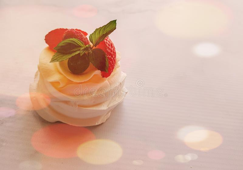 Pavlova mini cake with fruits and mint leaves in the stardust. royalty free stock image
