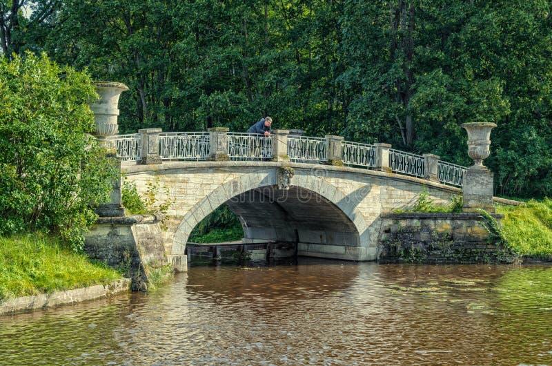 Pavlovsk park. A man fishing on the Visconti bridge. Pavlovsk (Saint Petersburg suburbs), Russia. August 27, 2016. Pavlovsk park. A man fishing on the Visconti stock image