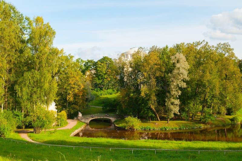 Pavlovsk parkerar territoriet den soliga aftonen med för den Pavlovsk slott- och kentaurbron för hösten i Pavlovsk, St Petersburg royaltyfri bild