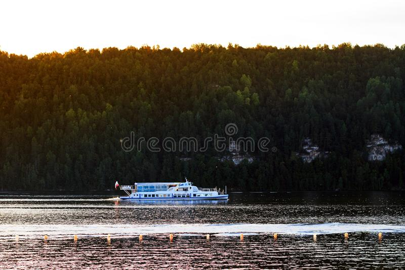 Pavlovsk Reservoir, Russia - August 10, 2018: ferry on background of mountaine forest, summer boat trip royalty free stock photo