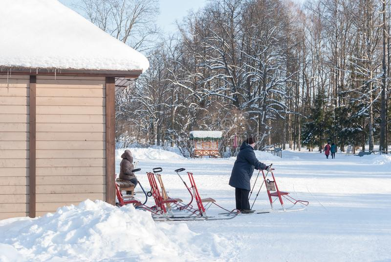 Pavlovsk, St. Petersburg, Russia - February 08, 2018: Rental of winter inventory. Elderly people hire winter sports equipment in P royalty free stock photo