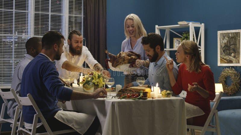 Pavo del día de fiesta de la porción de la mujer en cena con los amigos imagen de archivo libre de regalías