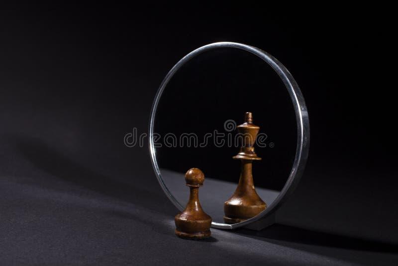 Pawn som ser i spegeln och ser en konung royaltyfria bilder