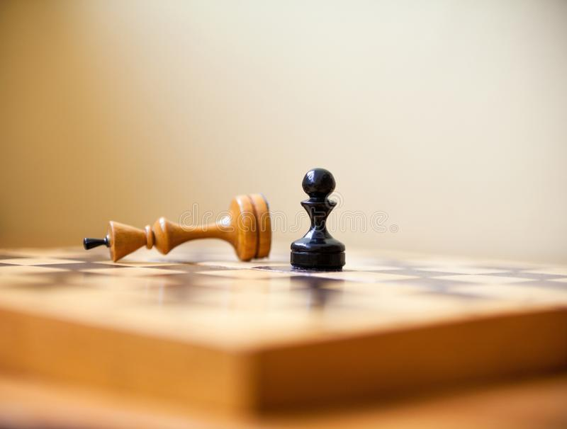Pawn wins a victory over the king. Chess pieces. Pawn wins a victory over the king. Wooden chess pieces on the chessboard. Chess game royalty free stock images