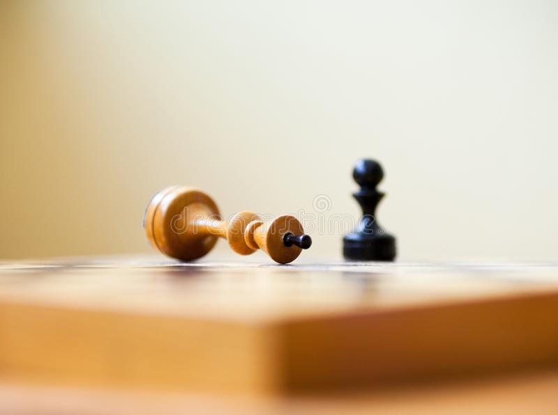 Pawn wins a victory over the king. Chess pieces. Pawn wins a victory over the king. Wooden chess pieces on the chessboard. Chess game royalty free stock image