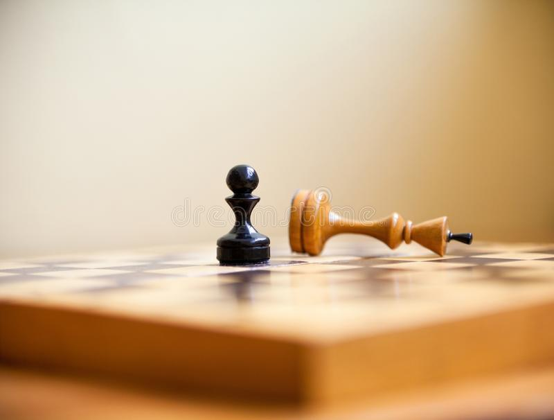 Pawn wins a victory over the king. Chess pieces. Pawn wins a victory over the king. Wooden chess pieces on the chessboard. Chess game royalty free stock photography
