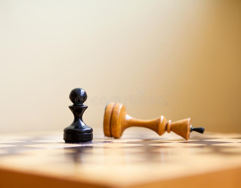 Pawn wins a victory over the king. Chess pieces. Pawn wins a victory over the king. Wooden chess pieces on the chessboard. Chess game stock photo