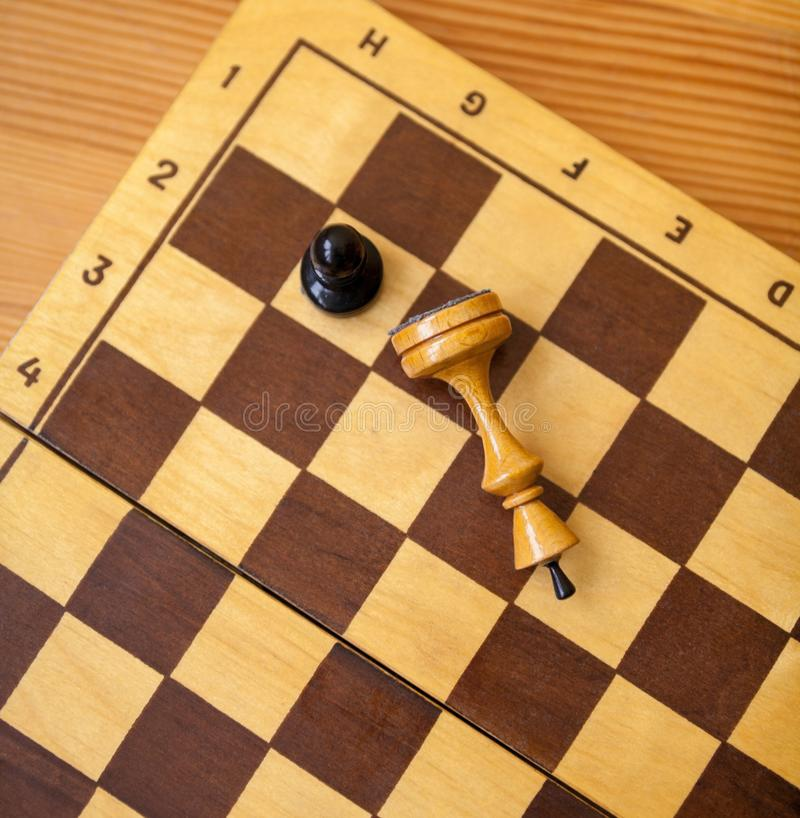 Pawn wins a victory over the king. Chess pieces. Pawn wins a victory over the king. Wooden chess pieces on the chessboard. Chess game. Top view stock photography