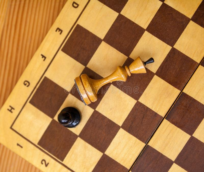 Pawn wins a victory over the king. Chess pieces. Pawn wins a victory over the king. Wooden chess pieces on the chessboard. Chess game. Top view royalty free stock photos