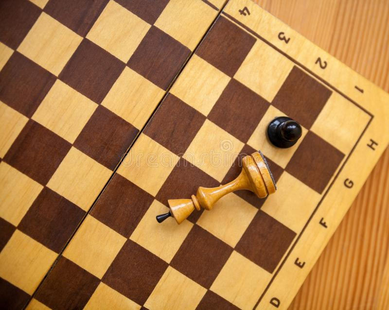 Pawn wins a victory over the king. Chess pieces. Pawn wins a victory over the king. Wooden chess pieces on the chessboard. Chess game. Top view royalty free stock images