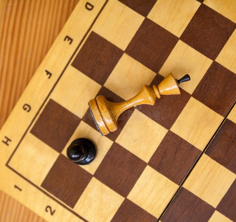 Pawn wins a victory over the king. Chess pieces. Pawn wins a victory over the king. Wooden chess pieces on the chessboard. Chess game. Top view stock photo