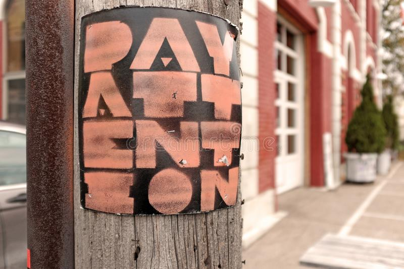 `Pay Attention` poster on a telephone pole referring to the US political environment stock photo