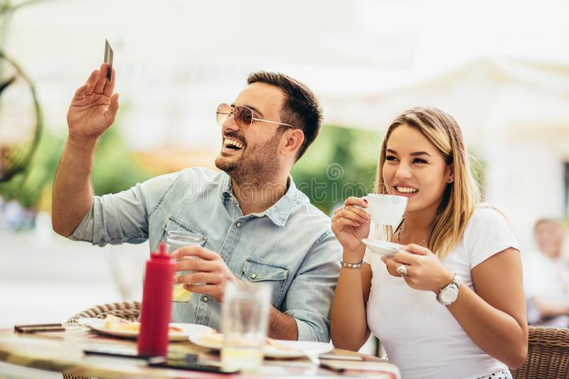 Pay the bill. Attractive young couple holding credit card while siting in cafe royalty free stock photos