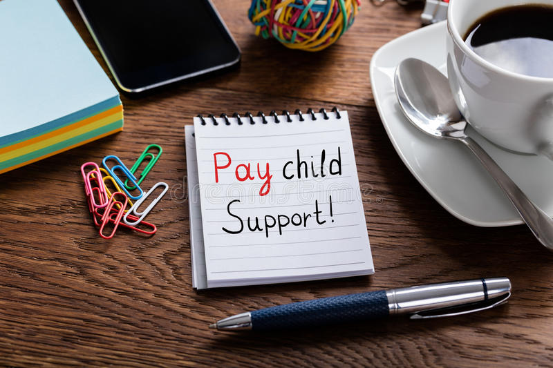 Pay Child Support Concept Written On Notepad. High Angle View Of Pay Child Support Concept Written On Notepad At Wooden Desk stock photography