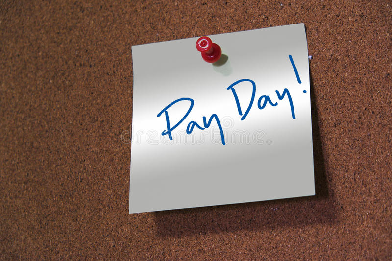 Pay day word. Pay day word written on a note which pinned on a cork noticeboard and focus with light royalty free stock image