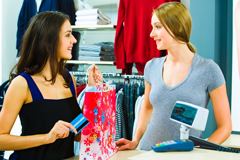 At the pay desk. Portrait of a buyer and a shop assistant looking at each other with smiles by the pay desk in the clothing department royalty free stock photo