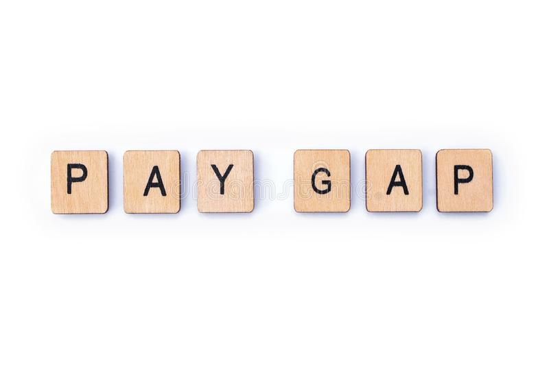 PAY GAP. Spelt out with wooden letter tiles royalty free stock photo