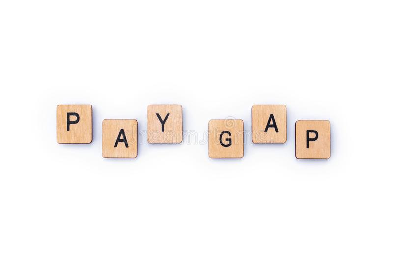 PAY GAP. Spelt out with wooden letter tiles royalty free stock images