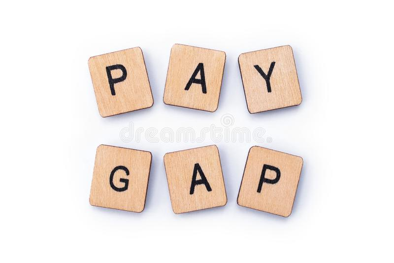 PAY GAP. Spelt out with wooden letter tiles stock images