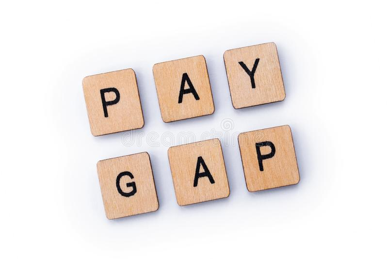 PAY GAP. Spelt out with wooden letter tiles stock image