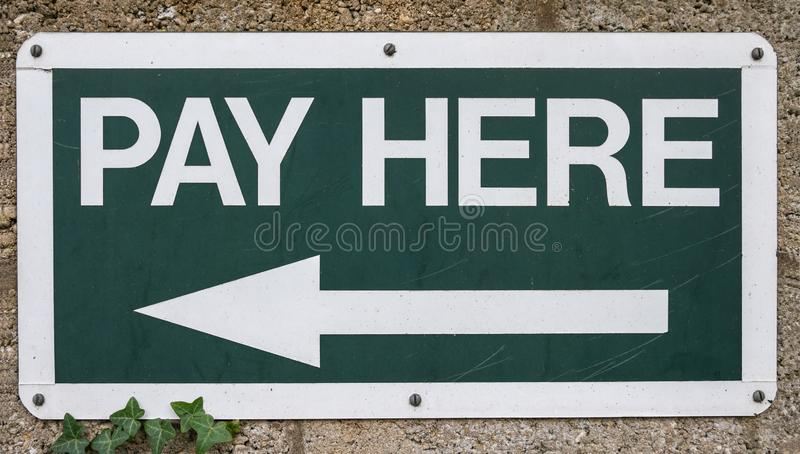 Pay Here sign. With arrow pointing to the left. White text on dark green background stock photography