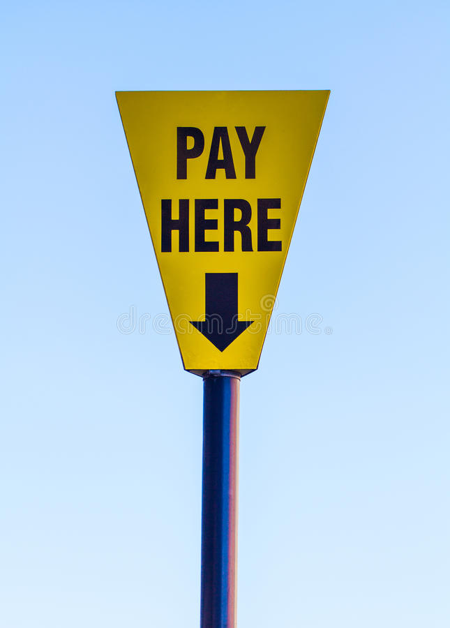 A Pay Here Sign. A yellow and blue triangular sign with the words Pay Here printed on and an arrow pointing downwards with a blue sky behind royalty free stock photos