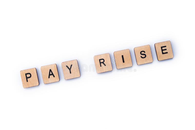 PAY RISE. Spelt out with wooden letter tiles royalty free stock photos