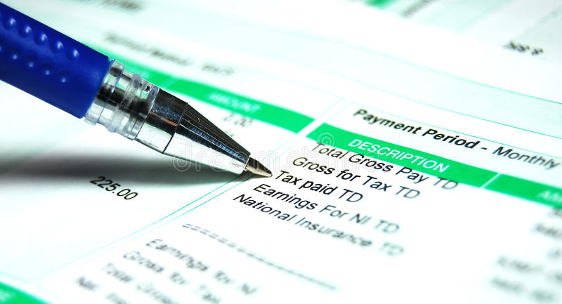 Pay slip tax. Pen indicating tax paid on a pay slip stock images