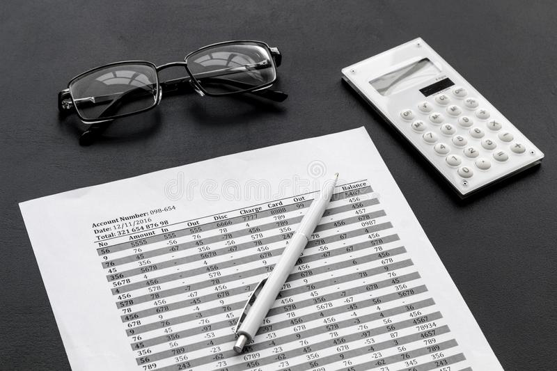 Pay taxes for business on office work desk with glasses and calculator black background royalty free stock image