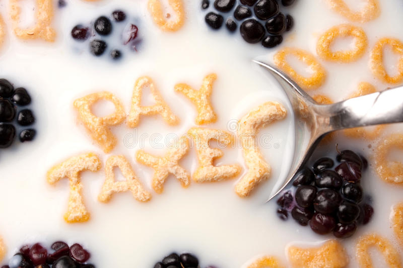 Pay Taxes Cereal Reminder. The words PAY TAXES spelled out of letter shaped cereal pieces floating in a milk filled cereal bowl royalty free stock photos