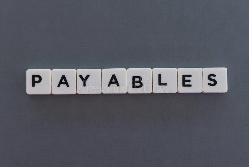 Payablesordet gjorde av fyrkantigt bokstavsord på grå bakgrund royaltyfri fotografi
