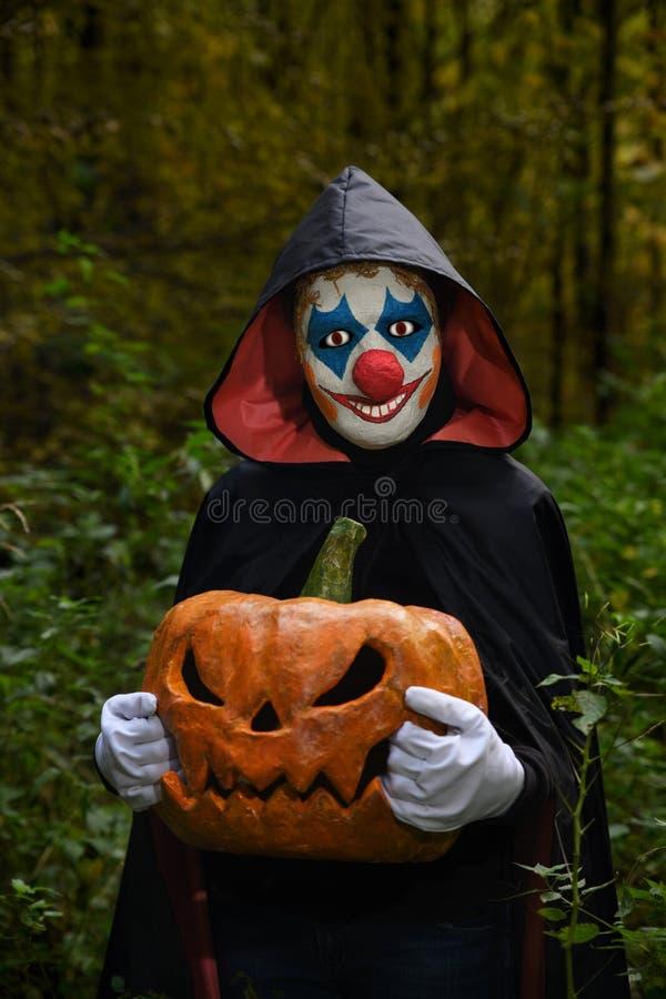 Payaso asustadizo en el bosque con una calabaza para Halloween imagen de archivo libre de regalías